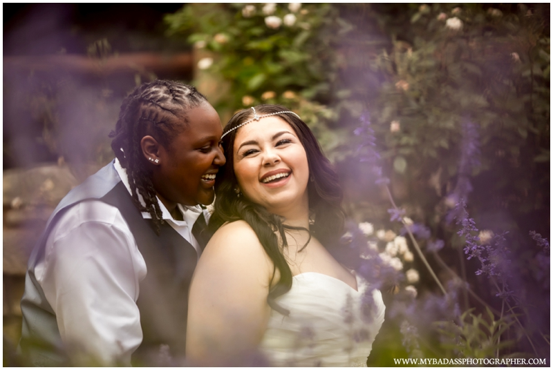 a happy LGBT lesbian couple poses in a garden in Georgetown Texas