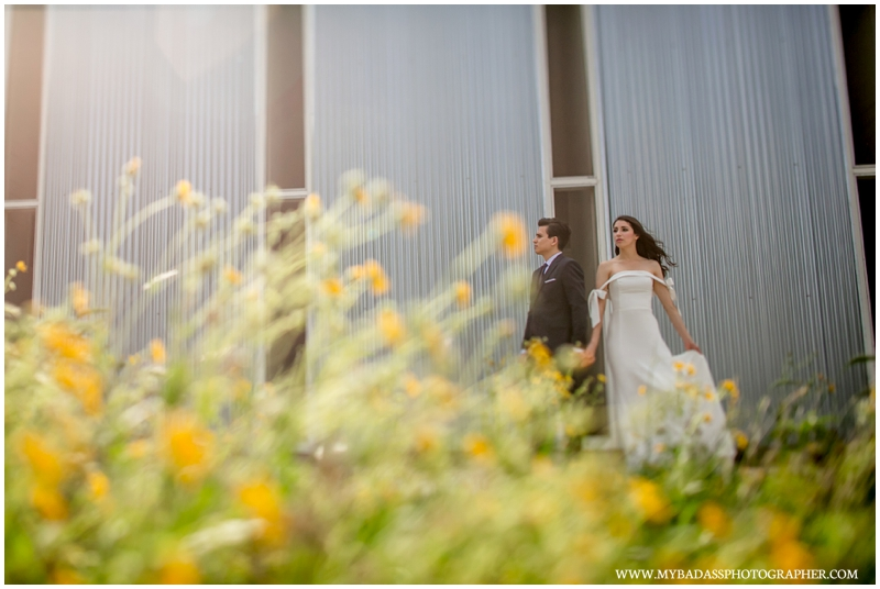 creative sunshine photograph at Prospect House with a brunette couple posing for their wedding day in flowers