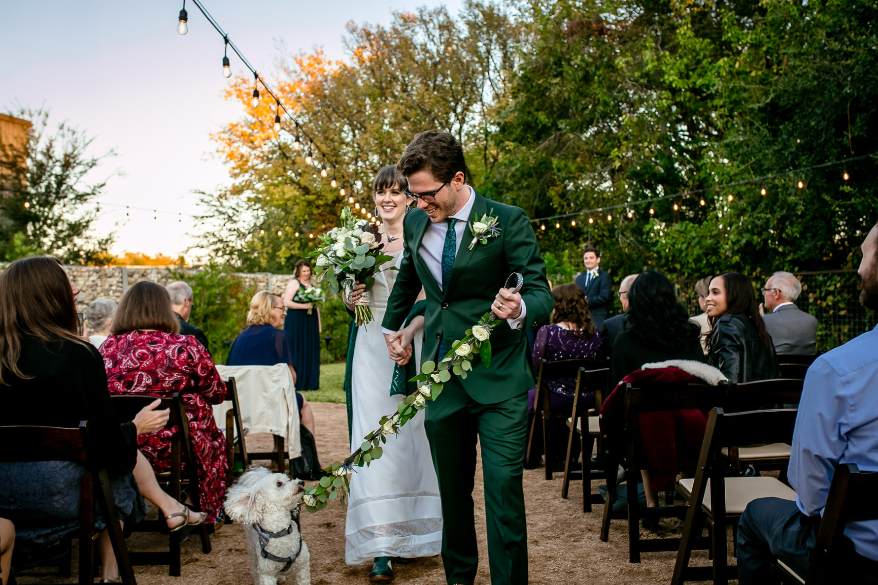 a bride and groom walk down the aisle with their dog